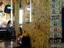 The walls are covered in dollar bills in the restaurant