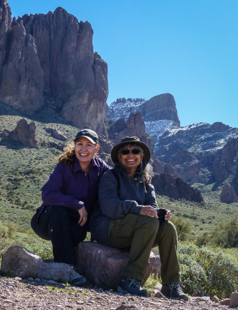 two hikers at the Superstition Mountains with a snow-capped Flatiron in the distance
