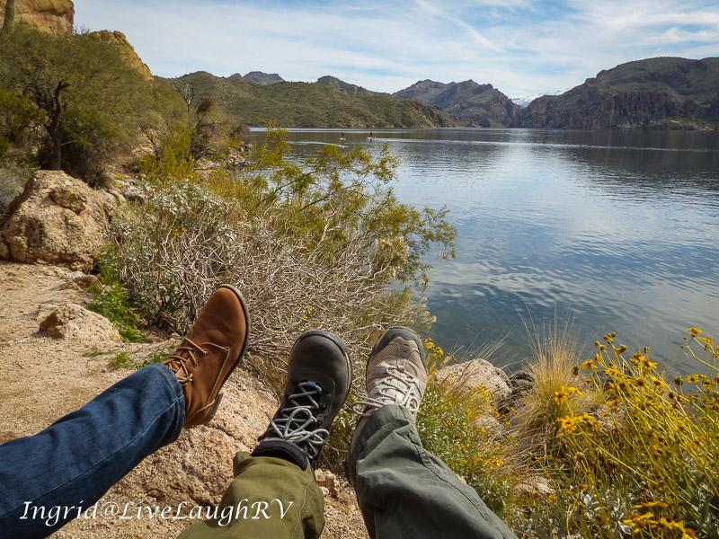 three different feet wearing hiking shoes photographed near a pristine lake near Phoenix, Arizona