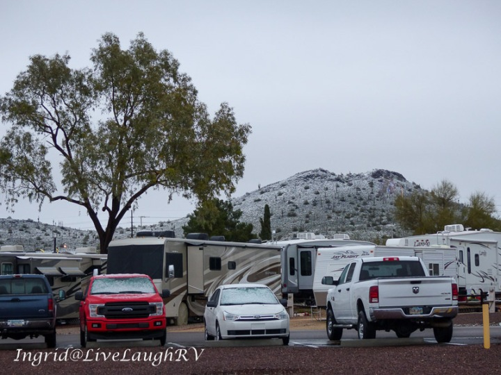 an RV park in Phoenix, Arizona with a snow coated hill in the background