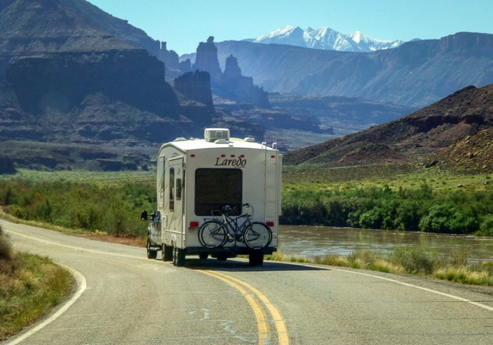 RV traveling down the road with scenic Moab, Utah in the background