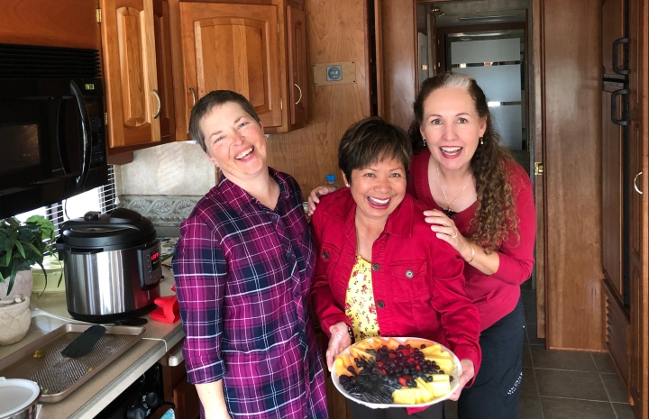 three ladies share food on Thanksgiving