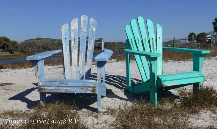 two aged adirondack chairs on a lone beach