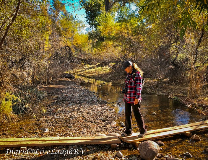 a female hiking across a creek in Arizona