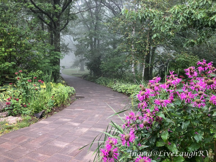 A brick paver trail in fog with pink flowers in foreground