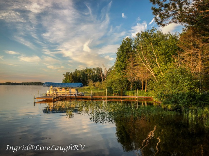 Reflections in a lake in northern Wisconsin, boat at a dock on a lake