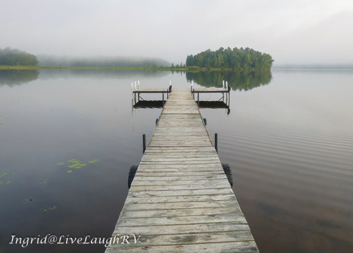 An inviting dock leading out to a fog covered morning