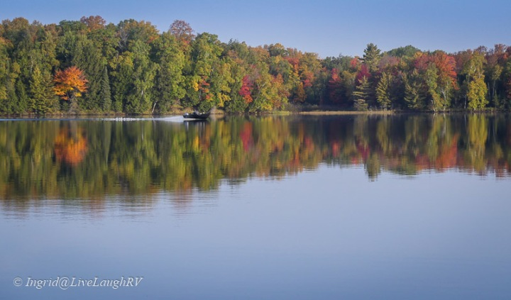 a boat on a lake with fall colors
