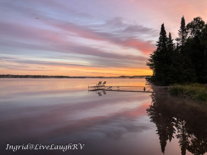 a pink sunrise over a Wisconsin lake. A pier in the distance reflected in the water.
