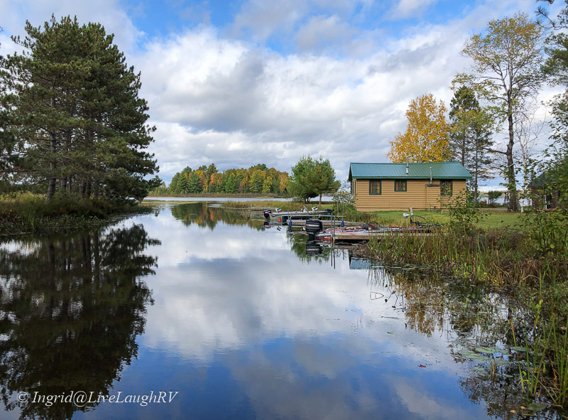 a cabin and boat docks on a reflective lake in Wisconsin