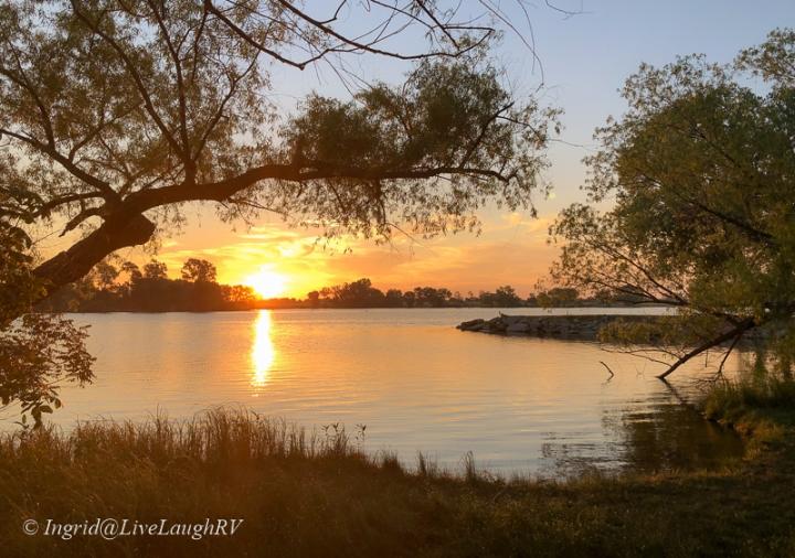 orange and yellow sunrise over a reflective lake