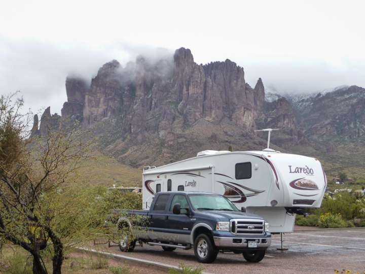 an RV camped at the base of the cloud covered Superstition Mountains with